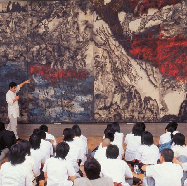 『沖縄戦の図』(丸木位里・丸木俊 1984年)修学旅行生に絵の解説をする佐喜眞道夫館長。