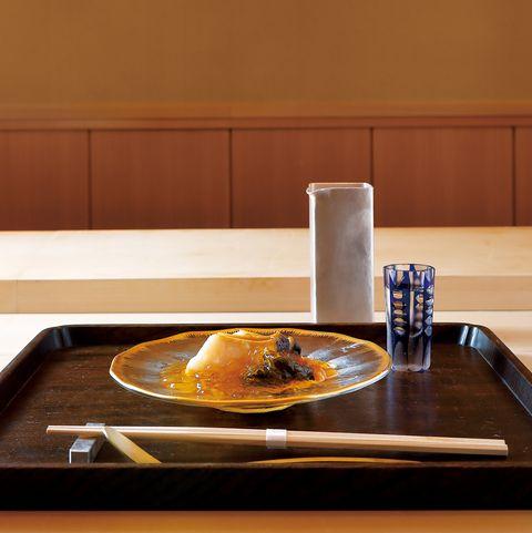 のぐち継のカウンターと店内。蒸し鮑にすっぽんの澄んだ煮凝りを合わせたひと皿は5品のコースから。上品な旨みが広がります。