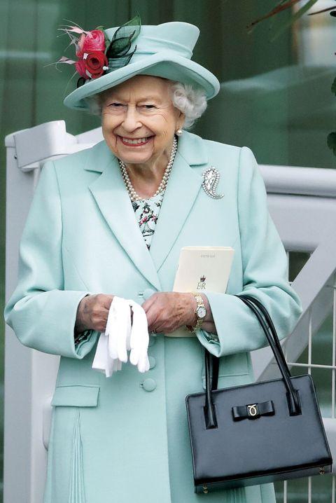 金具のモチーフがアイコニックな「ロウナー」のバッグは女王陛下のお気に入り。なかでもクラシカルな台形のハンドバッグは、長年不動の愛用モデルです。2021年6月のロイヤルアスコットでは、清々しい色の帽子とコートの装いの利かせ役に。