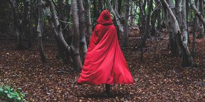 Figure in red cape going through forest