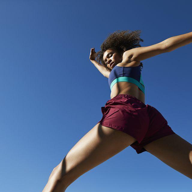 jonge vrouwelijke atleet springt in de blauwe lucht op zonnige dag