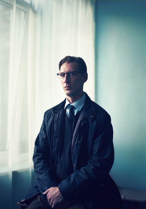 un hombre con abrigo sentado al lado de una ventana