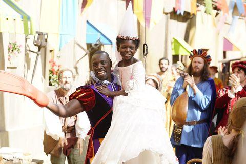 un principe lleva en brazos a una niña negra