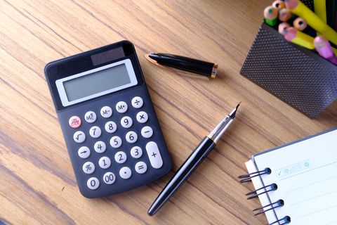 Financial notebook and pen on wooden table
