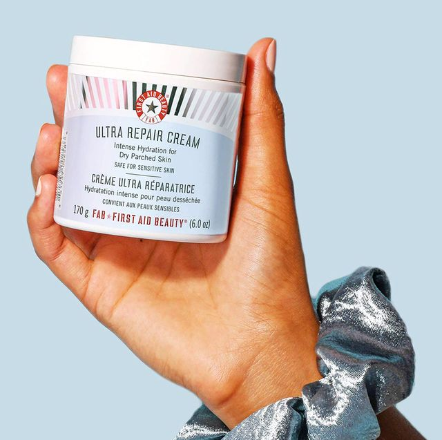 hand with scrunchie holding first aid beauty ultra repair cream