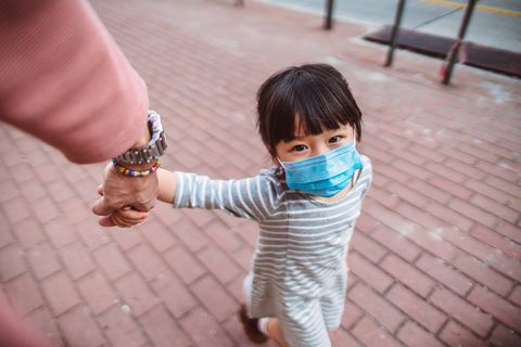 first person perspective of dad holding little daughter's hand who's wearing a medical face mask while they strolling on the street joyfully