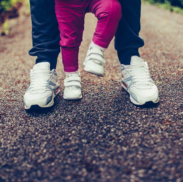 klein kind met schoentjes aan loopt met een ouder