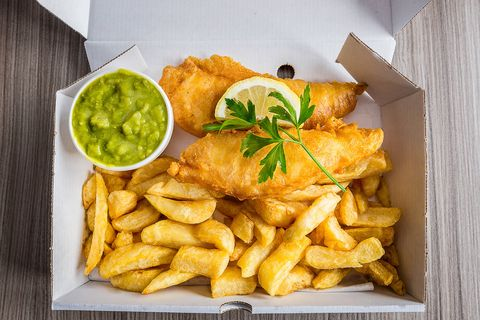 Fish and chips with peas and slice of lemon and garnish.