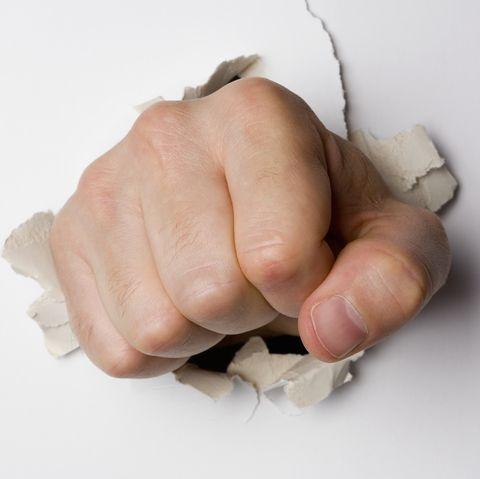 A fist breaking through a wall