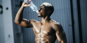 Fit and mascular man drinking water
