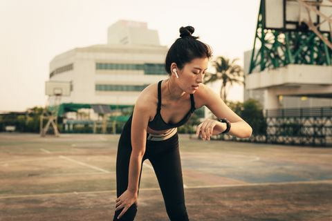 interval training fit asian woman looking at her smart watch while working out
