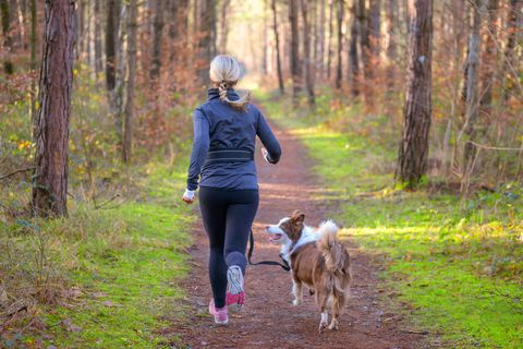 fit blond woman jogging with her dog