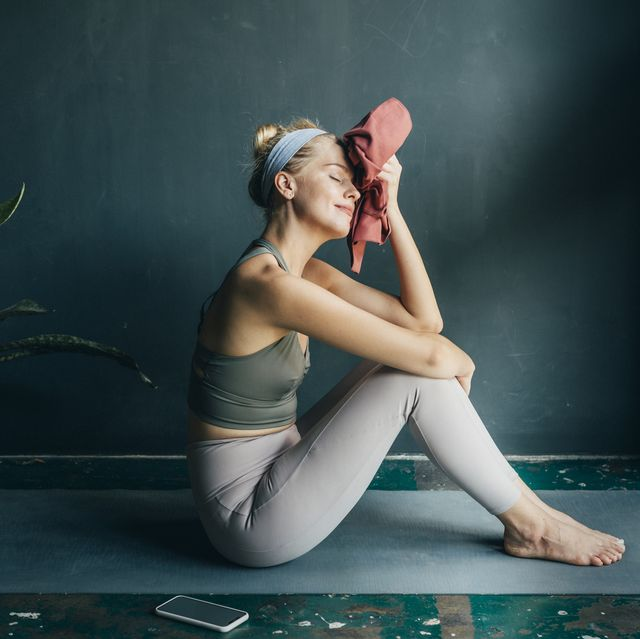 tired, but happy fit blonde woman wiping her face with a towel after a home workout