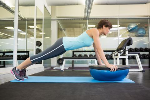 Fit brunette using bosu ball in plank position