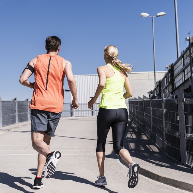 fit couple jogging in the city