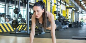 Fit girl doing plank exercise for back spine and posture. Sportswoman doing push-ups while legs hanging on elastic rope in gym