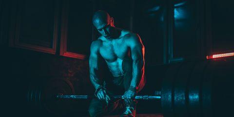 Fit man preparing for weightlifting in dark gym