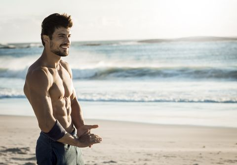 fit man relaxing on the beach