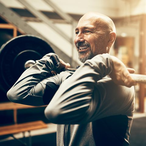 Fit mature man lifting weights and smiling in a gym