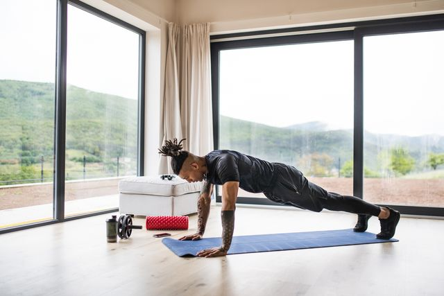 a fit mixed race man with dreadlocks doing exercise at home