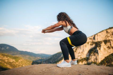 Fit woman squatting on mountain peak