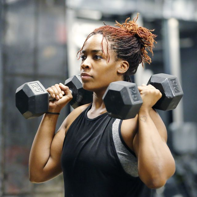 fit, young african american woman working out with hand weights in a fitness gym