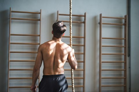 Fit Young Man In Gym Standing Topless , Holding A Climbing Rope. Rear View.