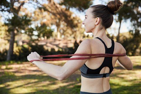 una chica con un top de deporte hace estiramientos con bandas elásticas