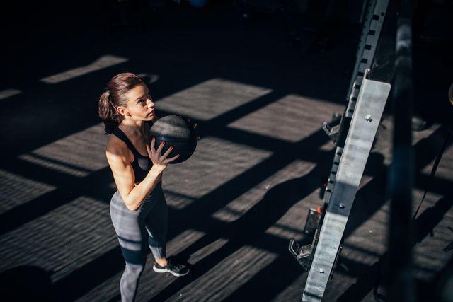 mujer entrenando con balón medicinal