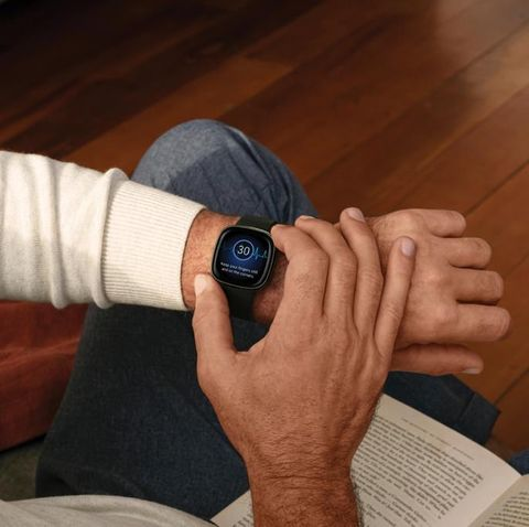man looking at his fitbit to track his health and fitness
