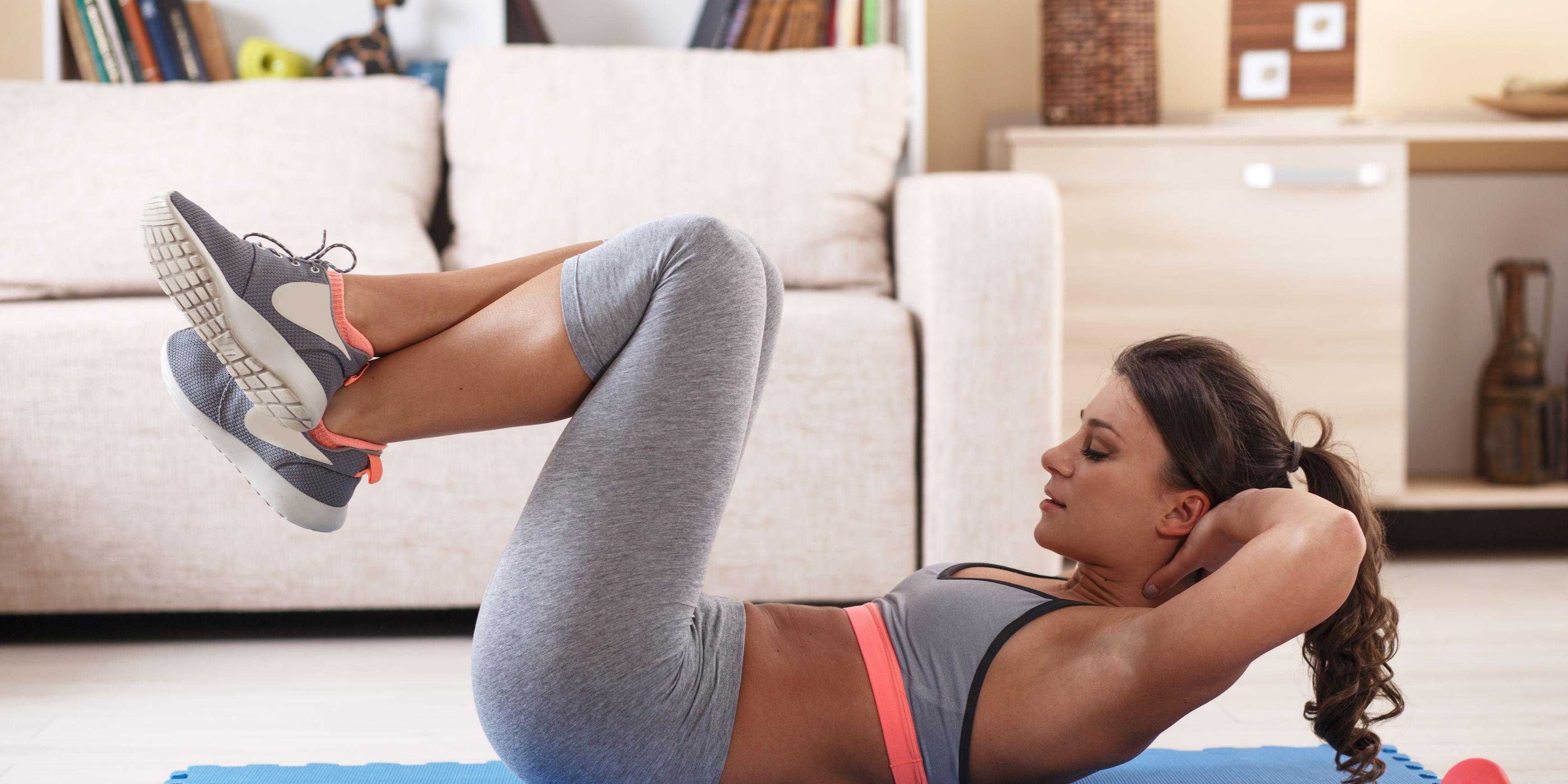Una ragazza che fa fitness a casa sul tappetino