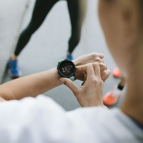fitness enthusiast setting timer on her watch