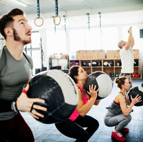 Fitness Enthusiasts Keeping Fit Using Weighted Balls