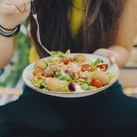 fitness girl eating fresh bowl salad at home