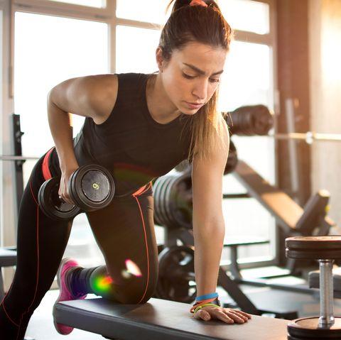 Fitness girl lifting dumbbell in the morning.