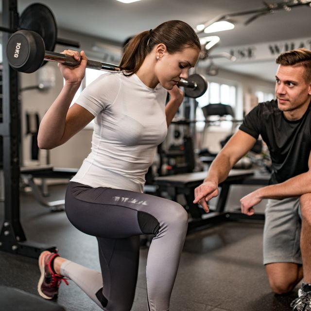 fitness instructor guiding young woman when she exercises