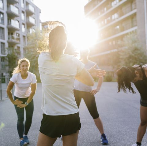 fitness instructor warming up with class outdoors
