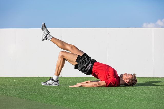 fitness man doing bodyweight glute single leg floor bridge lift exercises fit athlete training glutes muscles with one legged floor bridge butt raise in summer outdoor gym on grass