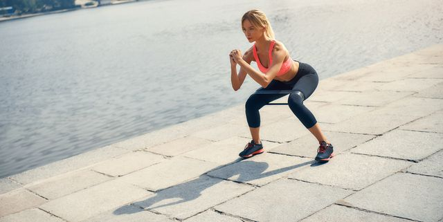 fitness model young and strong blonde woman in sports clothing exercising with a resistance band outdoors in front of the river