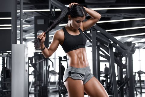 fitness sexy woman showing abs and flat belly beautiful muscular girl, shaped abdominal
