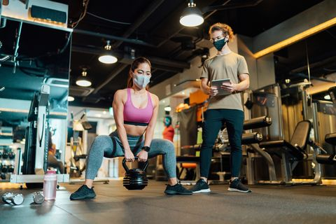 fitness trainer checking condition of female athlete in gym while both of them wearing protective face masks for illness prevention