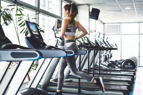 Mujer corriendo en la cinta del gimnasio