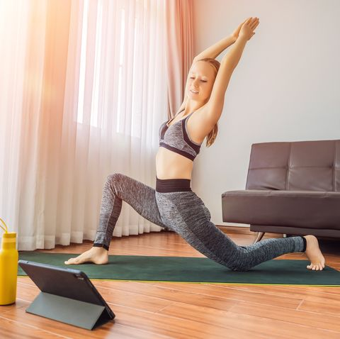 fitness woman exercising on the floor at home and watching fitness videos in a tablet people do sports online because of the coronovirus