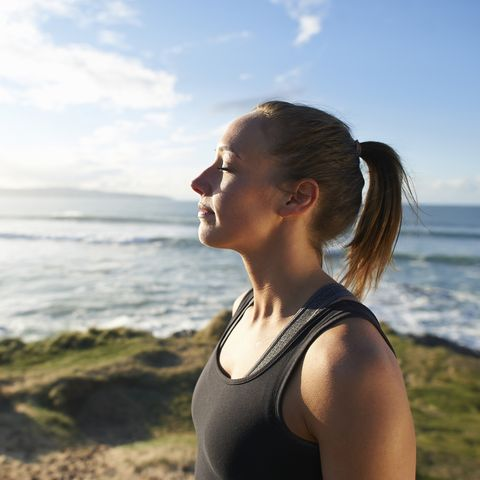 fitness woman profile with eyes closed beside sea