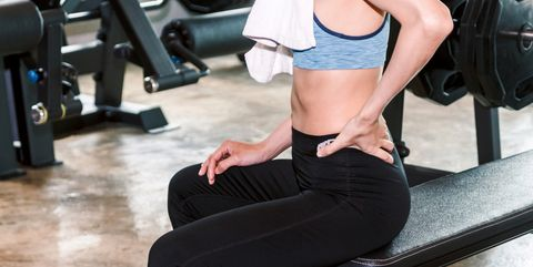 20c24118535b4 Fitness woman touching muscles of her lower back pain