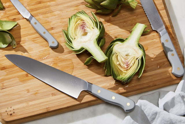 knives on cutting board with halved artichoke