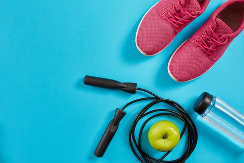 Flat lay of female sport equipments, jump rope, bottle of water and pink sneakers on blue background