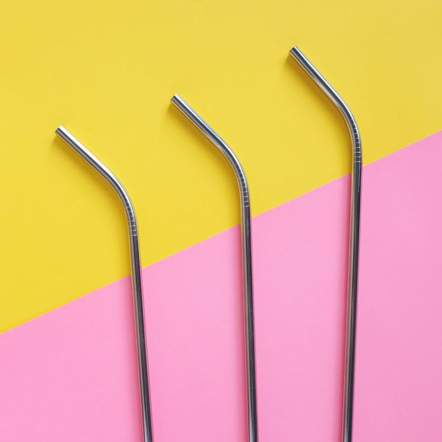 flat lay of metallic stainless straws for drink on bright pink and yellow background, sustainable product lifestyle and zero waste concept, copy space