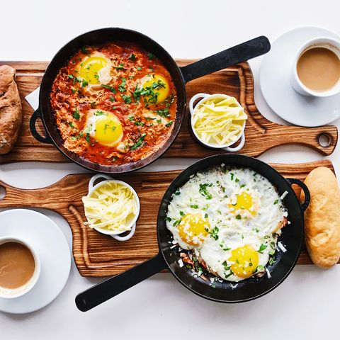 Flat lay with fried eggs in a skillet served on the table for two persons