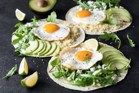 pain plat à l'avocat, œuf, fromage feta et salade de roquette